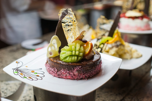 Reihen von lecker aussehenden desserts in wunderschönen arrangements. süßigkeiten auf banketttisch