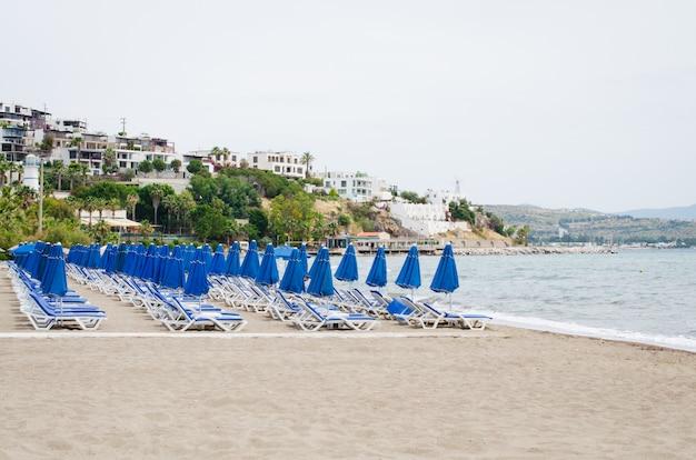 Reihen von leeren blauen sonnenliegen und sonnenschirmen am strand. kamelstrand in der türkei.
