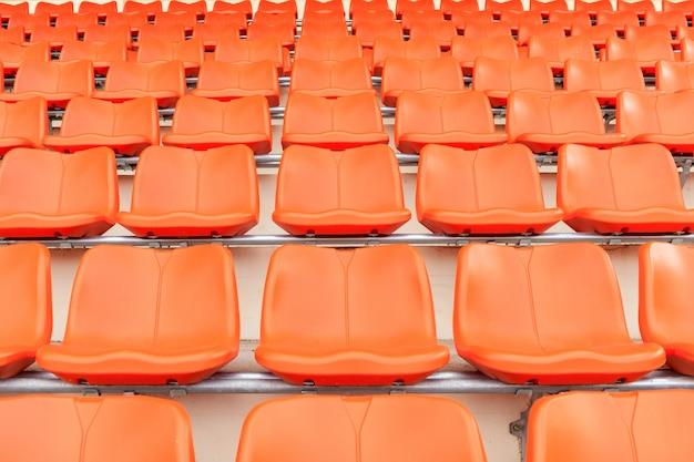 Reihen von leeren orange plastikhaupttribünensitzen am stadion.
