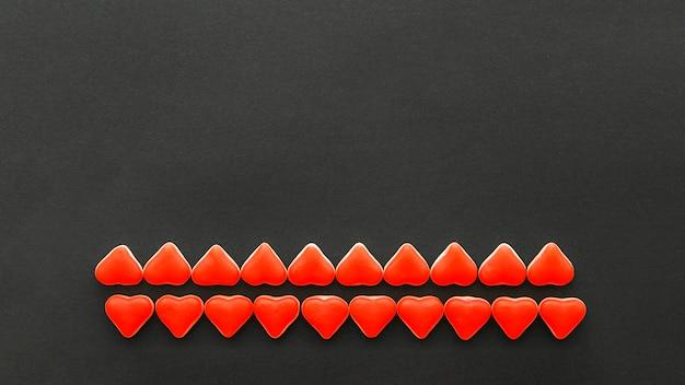 Reihen von roten herzformsüßigkeiten auf schwarzem hintergrund