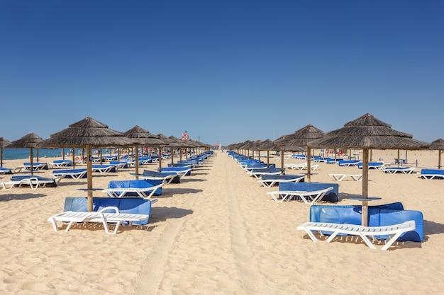 Reihen von sonnenliegen und sonnenschirmen zum sonnenbaden für touristen. tavira, portugal, algarve.