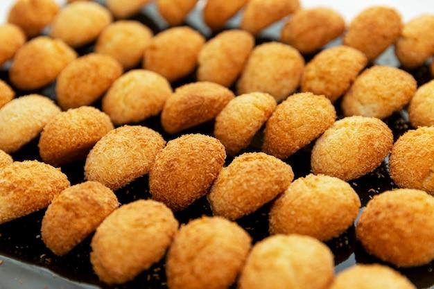 Reihen von süßen goldenen keksen auf einem tablett. leckeres gebäck.