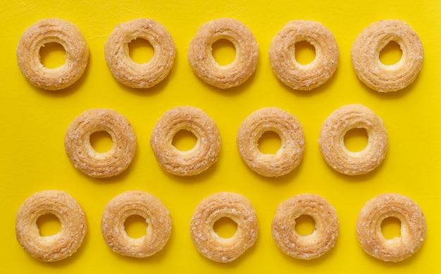 Reihen von vanillepudding-keksringen auf gelbem hintergrund, draufsicht, flacher lay