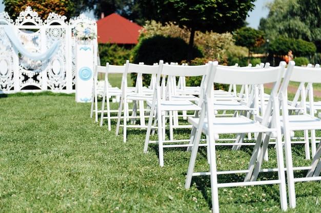 Reihen von weißen klappstühlen auf rasen