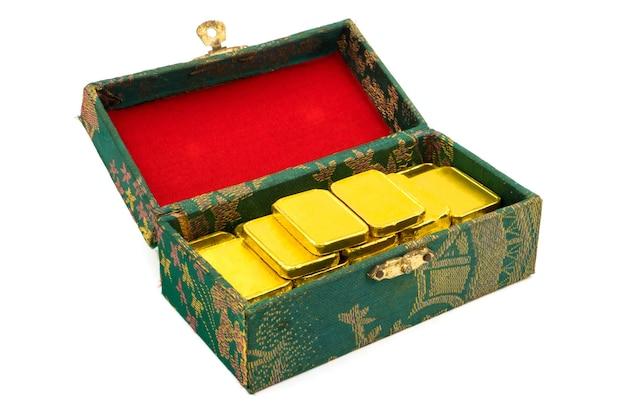Reine goldbarren im grünen kasten auf weißem hintergrund.