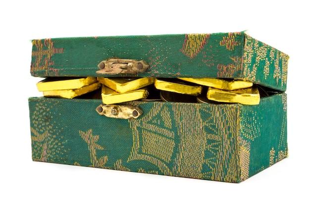 Reine goldbarren und -münzen im grünen kasten auf weißem hintergrund.