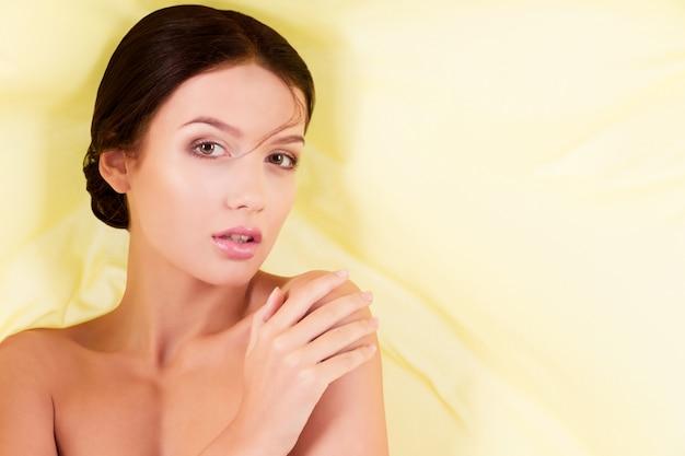 Reine saubere schönheitsfrau, die mit gelbem gewebe auf weiß aufwirft
