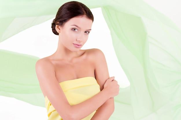 Reine saubere schönheitsfrau, die mit gewebe auf weiß aufwirft