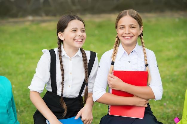 Reine unachtsamkeit. glückliche kindheit. zurück zur schule. teenager-schüler bereit für den unterricht. auf die prüfung vorbereiten. gemeinsam im freien studieren. kleine mädchen mit rucksäcken. kinder halten ein notizbuch, um notizen zu machen.
