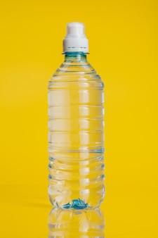 Reines wasser in der plastikflasche auf hellem gelbem hintergrund