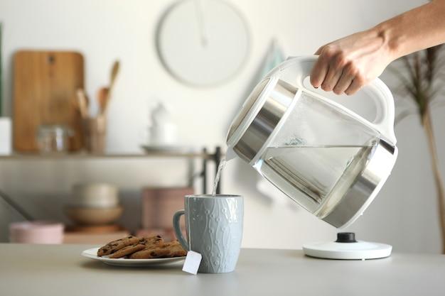 Reines wasser kocht in einem wasserkocher auf dem tisch in der küche