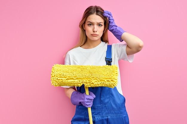 Reinige frau, die handschuhe trägt, die mopp über lokalem ernstem gesicht des rosa hintergrunds halten, das über frage nachdenkt