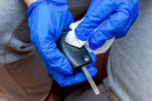 Reinigen, desinfizieren, abwischen der autoschlüssel mit einer hand in hand und serviette aus der nähe