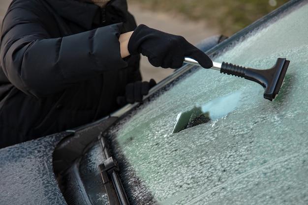 Reinigen sie das autofenster im winter vom schnee. reinigung von windschutzscheibenautos. eis und schnee von den fenstern entfernen.