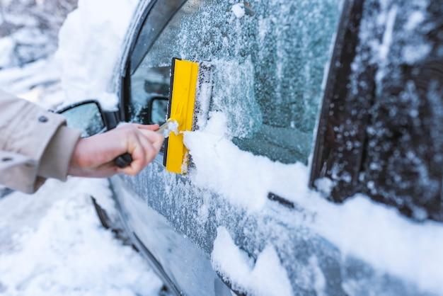 Reinigen sie das autofenster vom schnee. winter-scheibenreinigung.
