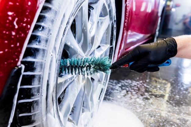 Reinigen sie das autorad mit einer bürste und wasser