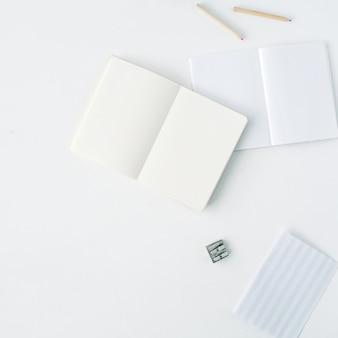 Reinigen sie das leere skizzenbuch, die stifte und den anspitzer auf weiß