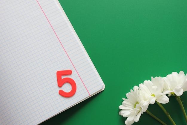 Reinigen sie das notizbuch in der schachtel und markieren sie fünf darin. drei weiße chrysanthemen