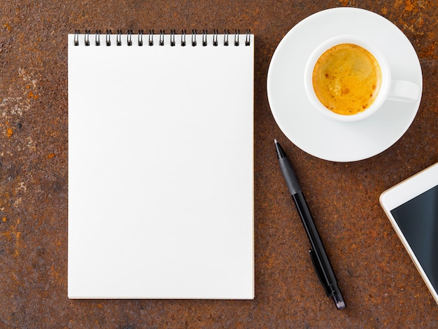 Reinigen sie das weiße blatt mit einem offenen, spiralgebundenen block, einem stift, einem mobiltelefon und einer tasse kaffee auf dem bügeleisen