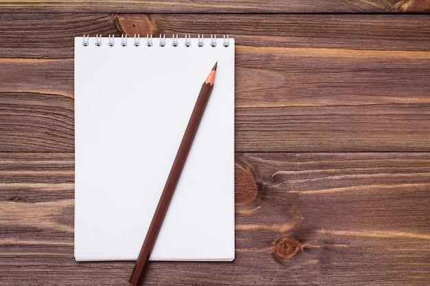 Reinigen sie den offenen notizblock zum schreiben auf einem spiralblatt und einen braunen bleistift auf holz
