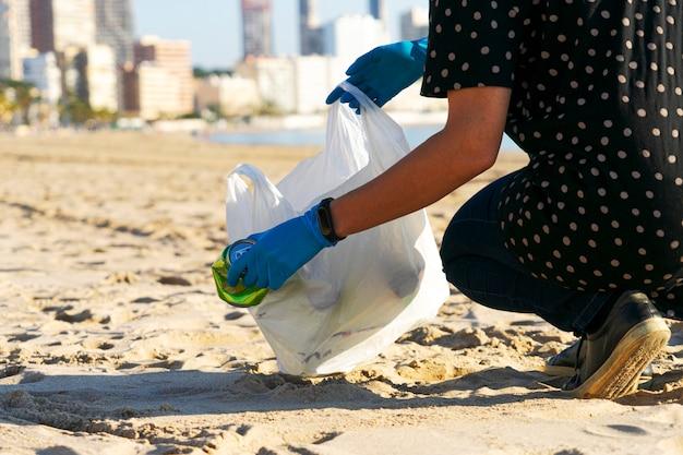 Reinigen sie den stadtstrand vom müll. frau hand, die leere alkoholfreie getränkedosen müll und plastikflaschen vom strand aufnimmt