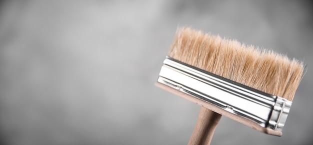 Reinigen sie frische neue pinsel zum malen auf grauem unscharfem betonhintergrund. schließen sie mit kopieren sie leeren raum für text. banner für werbung.