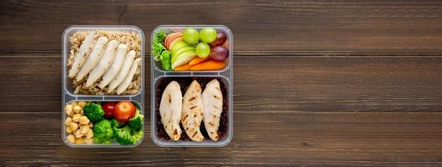 Reinigen sie gesundes, fettarmes essen in zwei essenssets zum mitnehmen auf holzbannerhintergrund-draufsicht mit kopienraum
