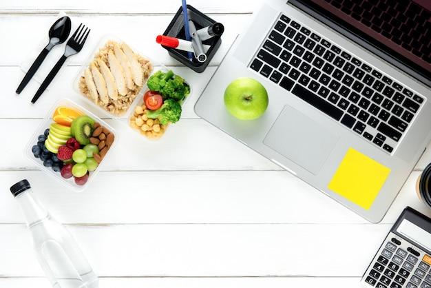Reinigen sie gesundes fettarmes lebensmittel mit laptop-computer auf arbeitstisch