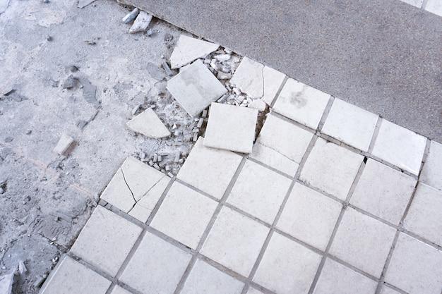 Reinigen sie weißen gebrochenen fliesenwandbeschaffenheitshintergrund. fliesenboden explodierte und rissig, weil für eine lange zeit verwendet, reparaturfliesen im haus