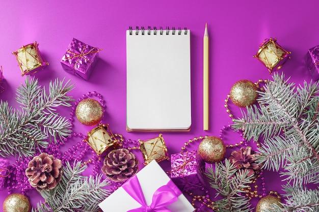 Reinigen sie weißen notizblock mit bleistift um weihnachtsdekorationen auf lila tisch. planung, wunschliste und auflösung 2021. die ansicht von oben