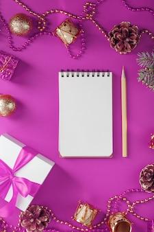 Reinigen sie weißen notizblock mit bleistift um weihnachtsdekorationen auf lila tisch. planung, wunschliste und auflösung. der blick von oben