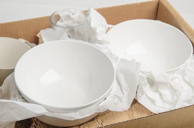 Reinigen sie weißes geschirr in papier, das in einem karton verpackt ist