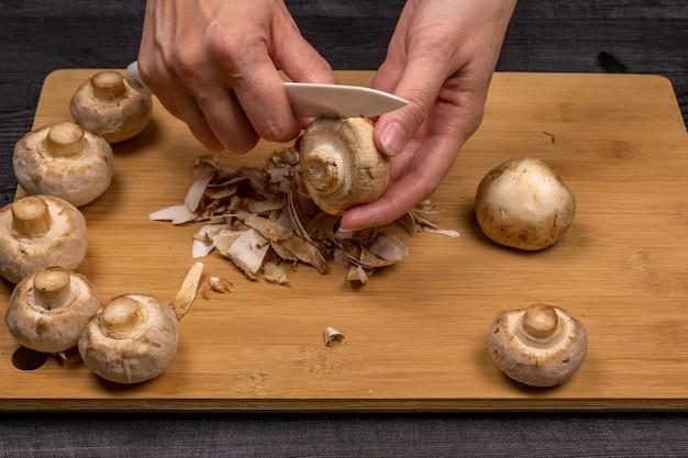 Reinigen und schneiden von champignons als teil der vorbereitung frischer champignons für das anschließende einfrieren