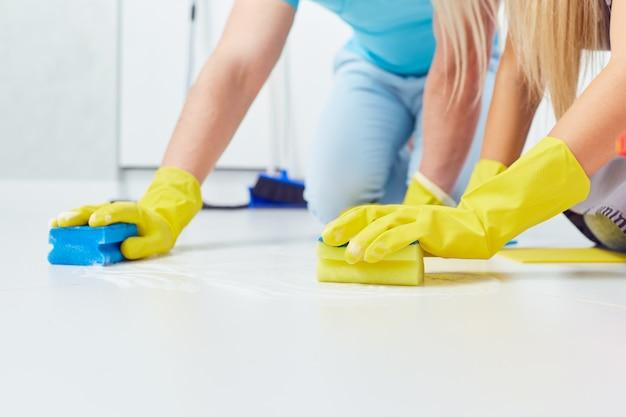 Reinigen, waschen. eine nahaufnahme von händen mit handschuhen beim reinigen des hauses.