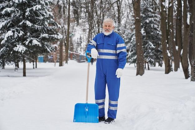 Reiniger im blauen overall, der auf schneeschaufel sich lehnt.