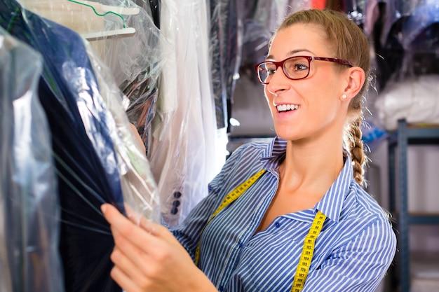 Reiniger im wäschereishop saubere kleidung überprüfend