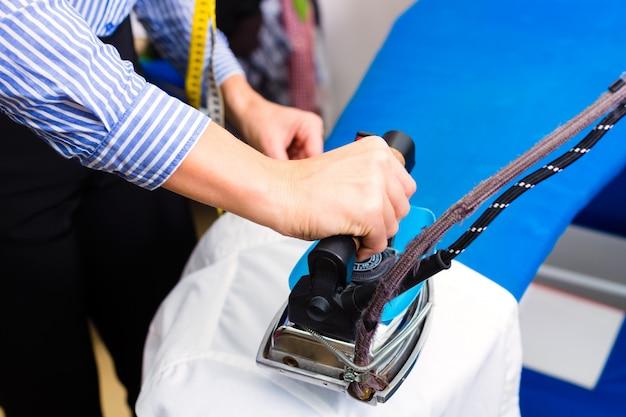 Reiniger in bügelnder jacke des wäschereishop