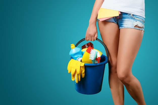 Reiniger mit einem eimer und reinigerhandschuhen und -backen auf einem blauen hintergrund