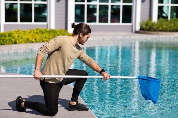 Reinigerpool des professionellen reinigungsarbeiters des jungen mannes mit schaufelnetz im freien.