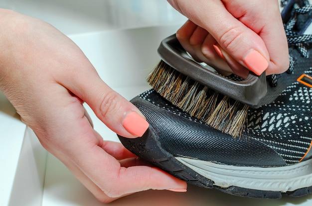 Reinigt sportschuhe, frau reinigt schuhe mit einer bürste. schmutzige laufschuhe reinigen