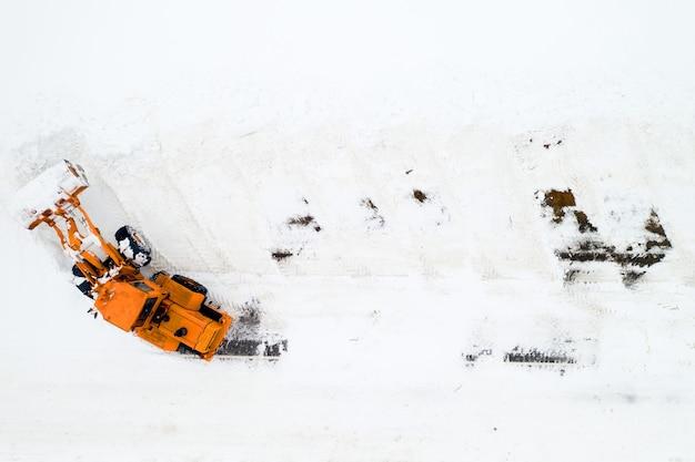 Reinigung der straßen von schnee nach starkem schneefall. der traktor reinigt die schneeansicht von oben.