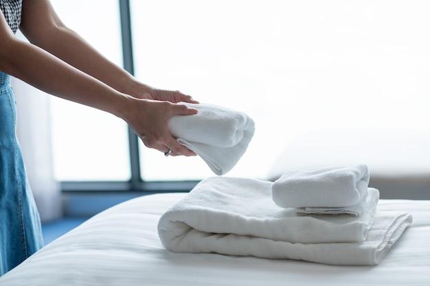Reinigung des hotels, badetuch auf weißem bett, zimmerservice
