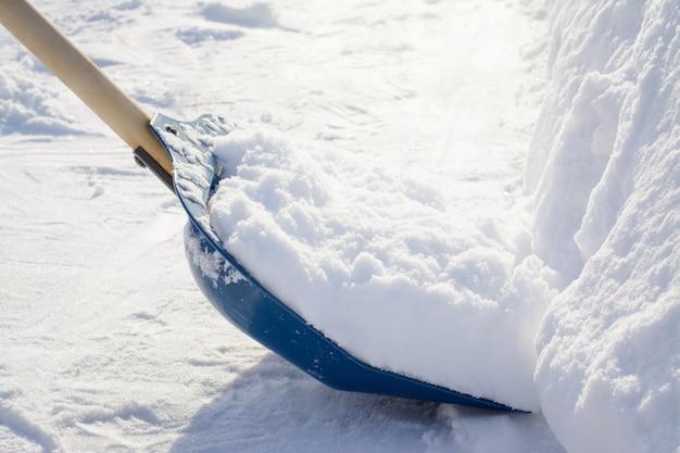 Reinigung des schnees mit einer schaufel auf dem land nach starkem schneefall