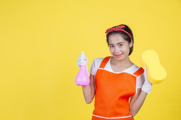 Reinigung eine schöne frau mit einem reinigungsgerät auf einem gelb.