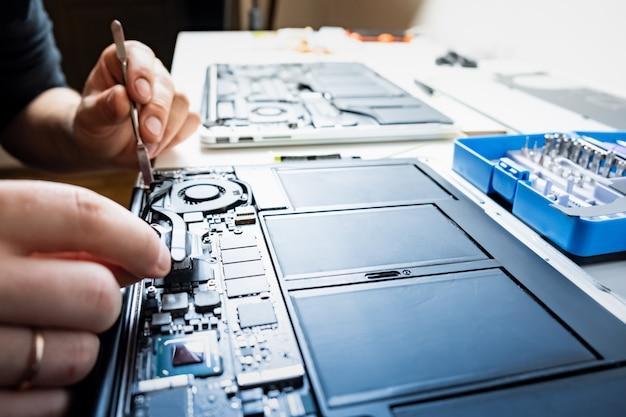 Reinigung eines laptops bei einem professionellen service. person führt regelmäßigen service durch und ändert wärmeleitpaste von modernen tragbaren computern, selektiver fokus