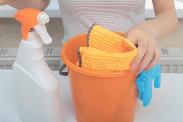 Reinigung nach reparatur, fassadenreinigung. junges mädchen mit reinigungsmitteln für badewannen, waschbecken, toiletten, schwämme und lappen