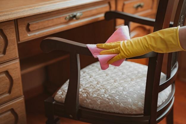 Reinigung und wartung des holzstuhl-tisches mit lappen und reinigungsmittel