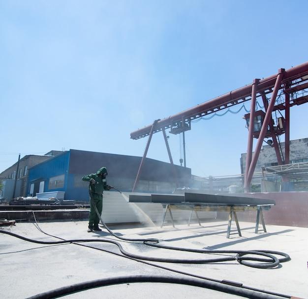 Reinigung von metall durch sandstrahlen arbeiter, der die reinigung durch sandstrahlen von metall durchführt