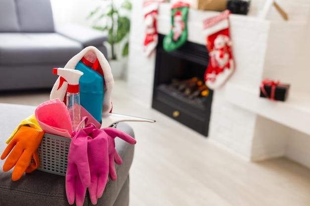 Reinigung vor weihnachten. mehrfarbige reinigungsmittel. schwämme, lappen und spray mit festlicher dekoration vor modernem wohnhintergrund