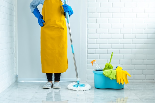 Reinigungs- und reinigungskonzept, glückliche junge frau in den blauen gummihandschuhen, die staub mit mopp abwischen, während sie auf boden zu hause reinigen